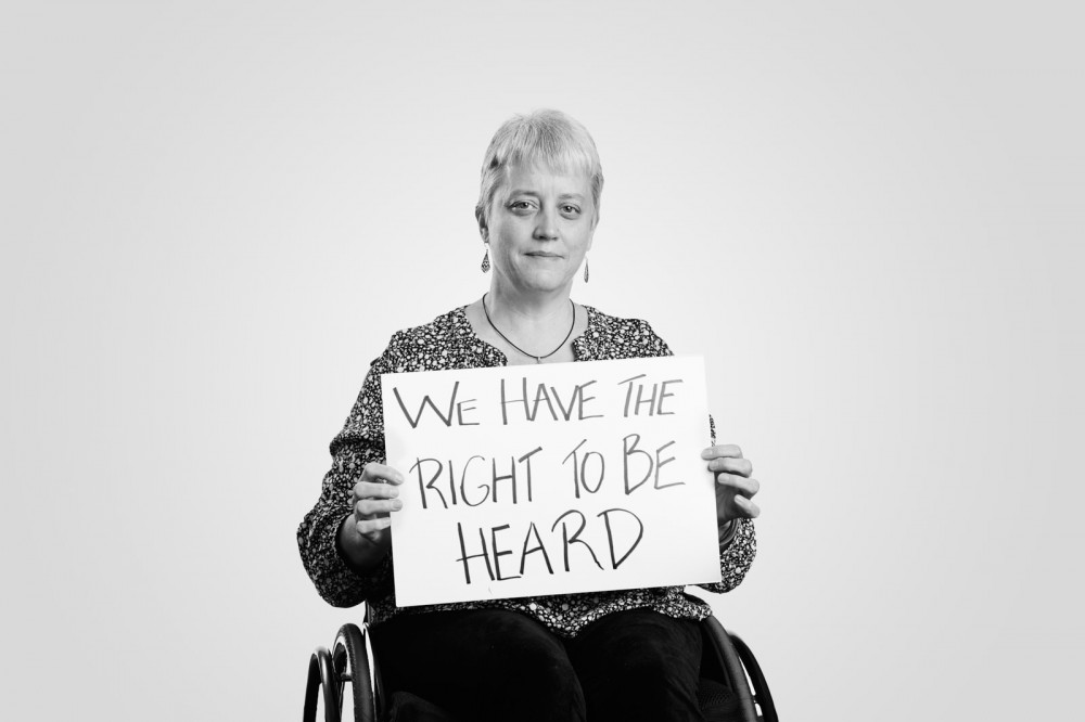 Louise, who uses a wheelchair, holds a handwritten sign: We Have the Right to Be Heard